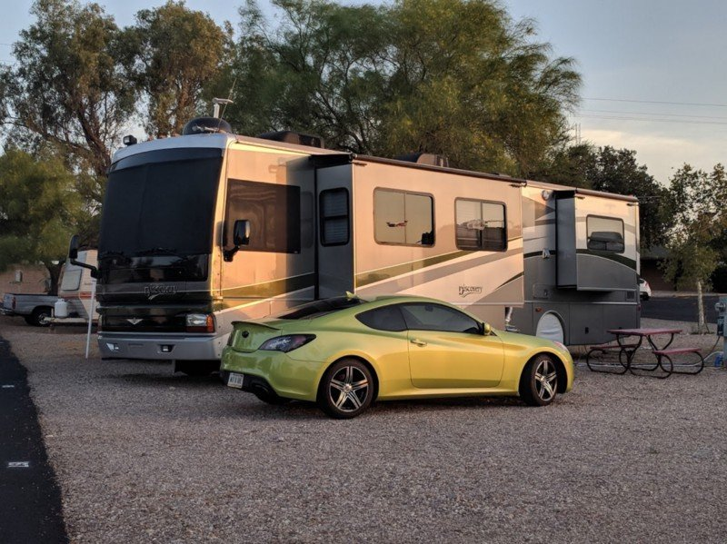 green motorhome with a green car parked beside it