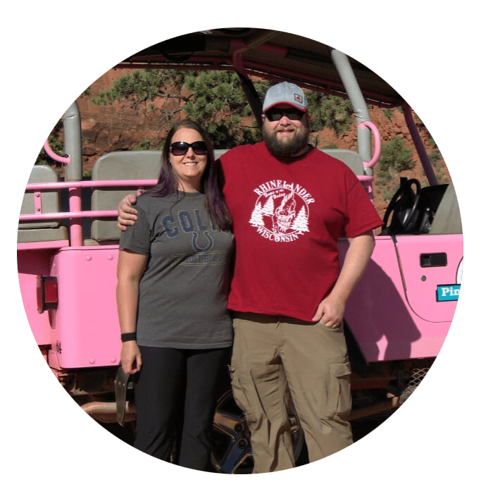 man and woman in their 30s standing in front of a pink Jeep