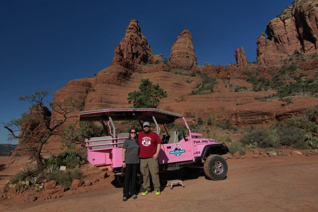 man and woman standing in front of a pink jeep by red rocks